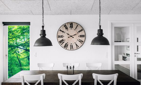 Retro clock over a table on a wall in a living room with green trees outside in the spring