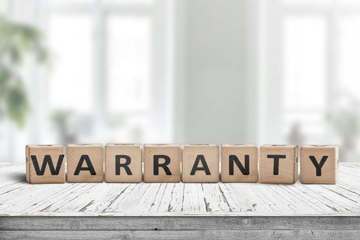 Warranty sign on a wooden desk in a bright environment with green plants
