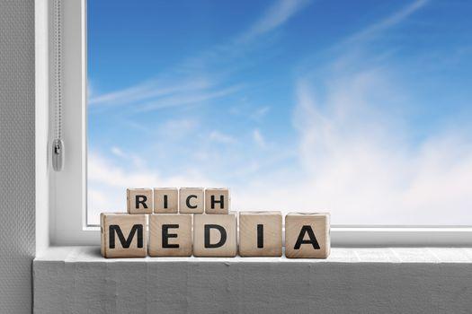 Rich media sign written on wooden blocks in a window with a blue sky outside