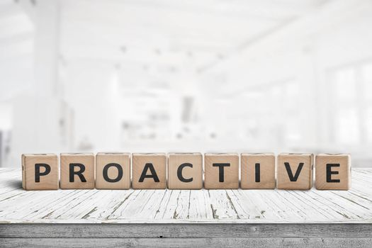 Proactive sign on a wooden table in a bright office in daylight