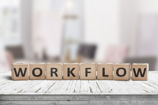 Workflow sign in a bright office on a wooden desk with table and chairs in the background