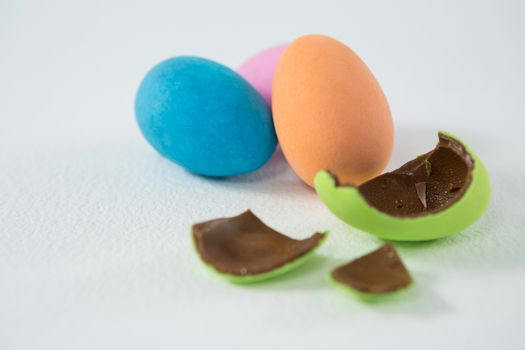 Broken chocolate Easter egg against three chocolate Easter egg