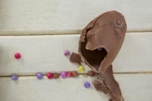 Broken chocolate Easter egg on wooden plank