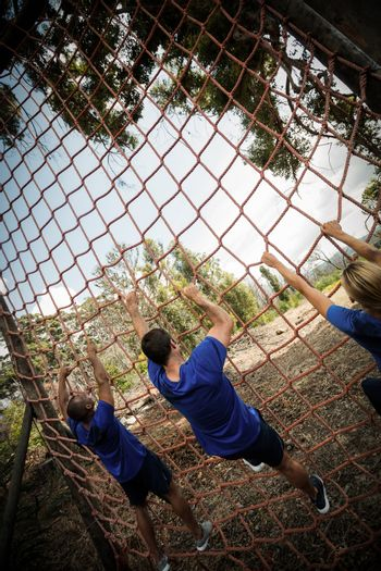 People climbing a net during obstacle course in boot camp