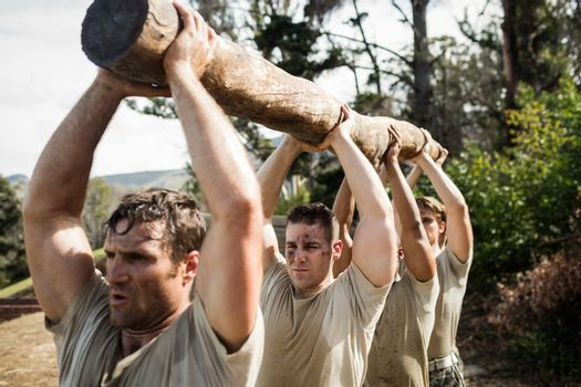 Soldiers carrying a tree log
