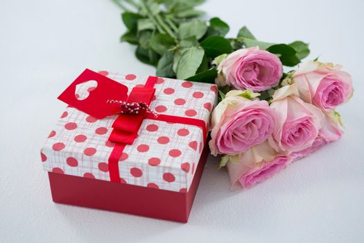 Close-up of gift box with bunch of rose on white background