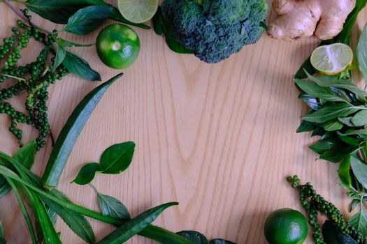 Background with assorted green vegetables of ripe fresh broccoli, ginger, lime, avocado, green pepper, Green okra and basil leaves on wooden background.