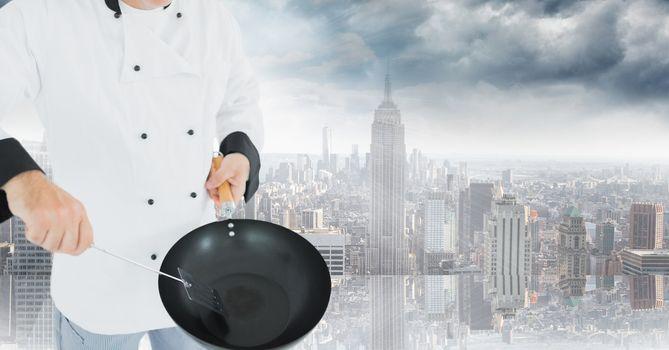 Chef with wok against blurry skyline