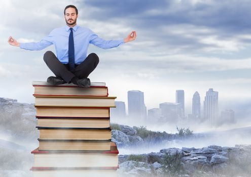 Businessman sitting meditating on Books stacked by distant city