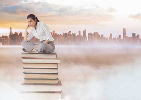 Businesswoman sitting on Books stacked by distant city