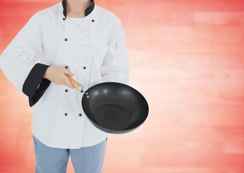 Chef with wok against blurry red wood panel