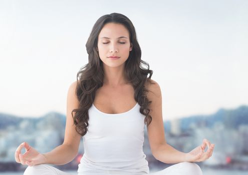 Woman meditating by hills
