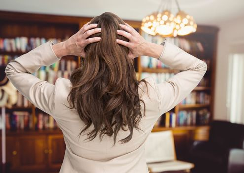 Stressed woman by chandelier and bookshelves in room