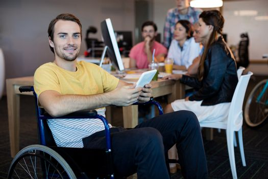 Physically disabled man on wheelchair using tablet in office
