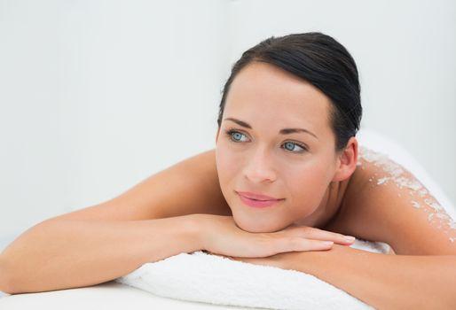 Peaceful brunette lying with salt scrub on back