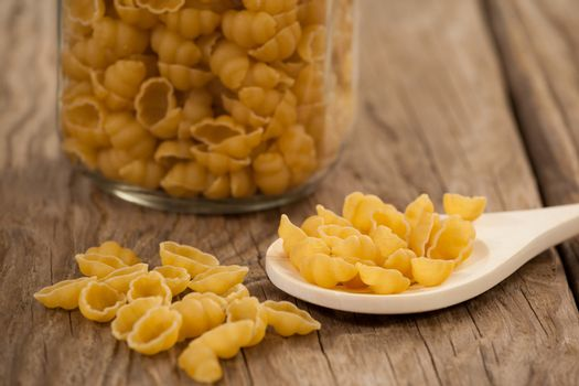 Conchiglie pasta spilling out of jar and spoon