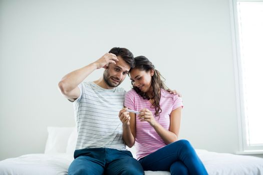Couple finding out results of a pregnancy test in bedroom