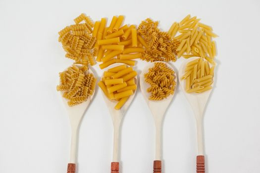 Varieties of pasta spilling out of spoons