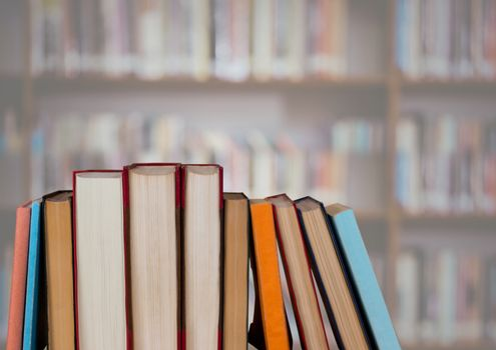 Standing books against blurry bookshelf
