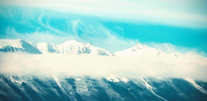 Snowy mountain range against blue sky