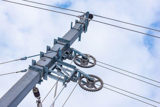 Railway electrification system details- electric power overhead line, steel pylon close up against cloudy, blue sky.