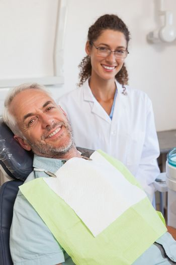 Patient and dentist smiling at camera at the dental clinic