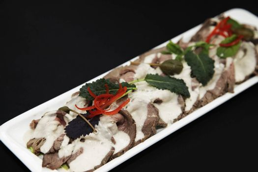 meat appetizer with cream sauce in a white rectangular plate