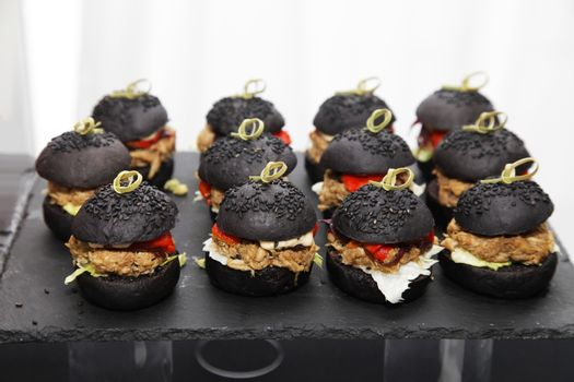 Mini burgers with black bun, stuffed with beef and tomato, sprinkled with black sesame seeds
