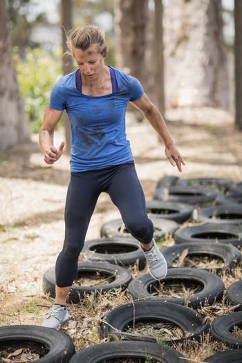 Woman running over the tyre during obstacle course