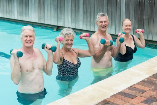 Swimmers weightlifting in swimming pool