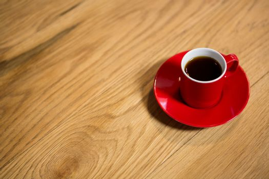Red cup and saucer on table in cafeteria