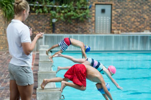 Female instructor monitoring time at poolside