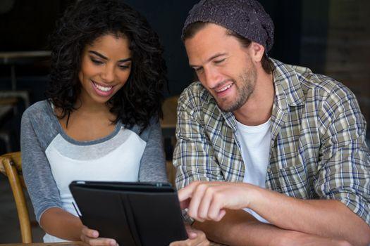 Friends using digital tablet in coffee house