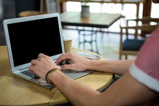 Man using laptop at table in coffee house