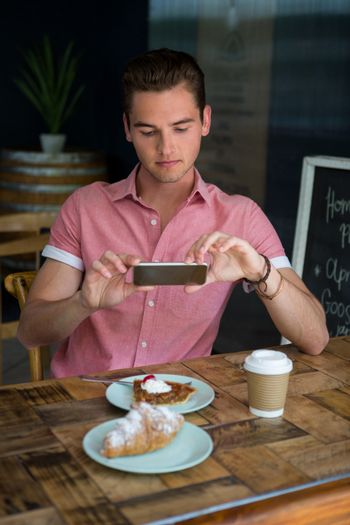 Man photographing food on table in coffee house