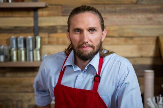 Confident male barista in carefetia