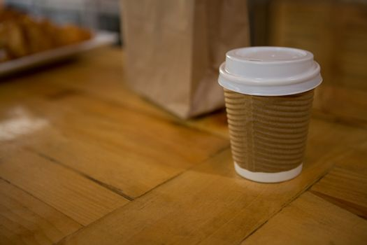 Disposable coffee cup on table in cafe