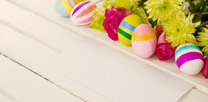 High angle view of painted Easter eggs with flowers and envelope on wooden table