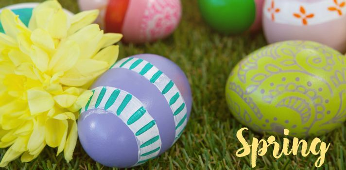 Easter greeting against painted easter eggs with flowers on grass