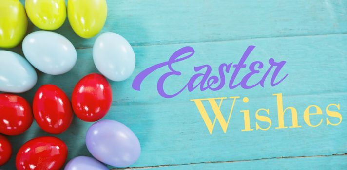 Easter greeting against colorful easter eggs on wooden surface