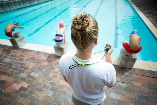 Female instructor monitoring children at poolside
