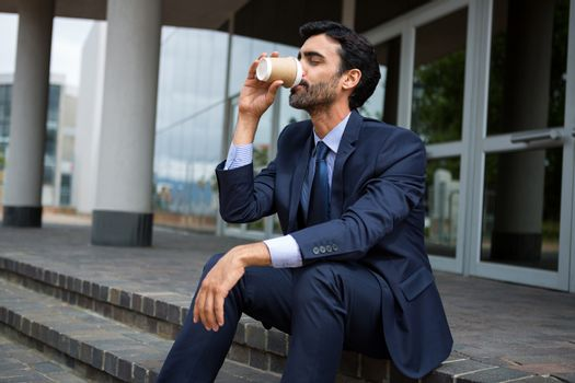 Businessman drinking coffee from disposable cup