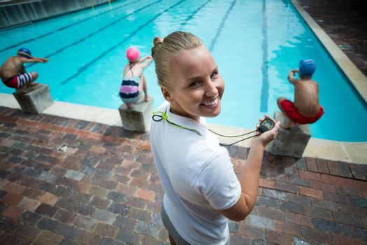Cheerful Instructor monitoring children at poolside
