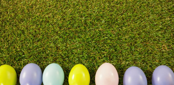 Overhead shot of colored Easter eggs on green grass