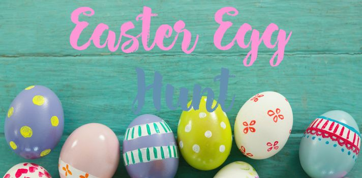 Easter greeting against painted easter eggs on wooden surface