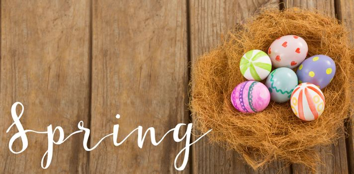 Easter greeting against painted easter eggs in nest
