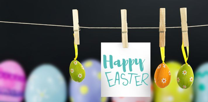 Easter greeting against painted easter eggs with various patterns chalkboard
