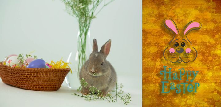 easter bunny with greeting against yellow paint splashed surface