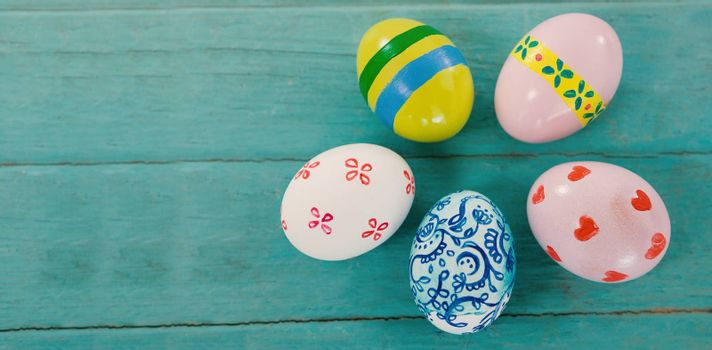 Overhead view of multicolored Easter eggs against wood background