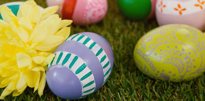 Painted easter eggs with yellow flowers on grass
